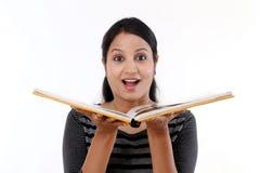 Mujer joven emocionada que lee un libro Imágenes de archivo libres de regalías