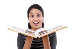 Mujer joven emocionada que lee un libro Imagenes de archivo