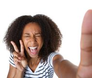 Mujer joven emocionada que muestra el signo de la paz en selfie Foto de archivo libre de regalías