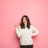 Mujer joven emocionada que señala su finger hacia arriba Fotografía de archivo libre de regalías