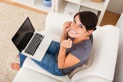 Mujer joven emocionada que se sienta con el ordenador portátil Imagenes de archivo