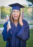 Mujer joven emocionada que sostiene el diploma en casquillo y vestido Fotografía de archivo libre de regalías