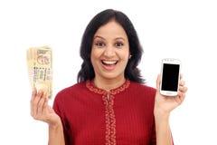 Mujer joven emocionada que sostiene moneda india y el teléfono móvil Foto de archivo