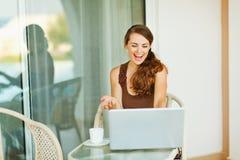 Mujer joven emocionada que trabaja en la computadora portátil en terraza Imagen de archivo