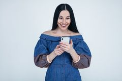 Mujer joven emocionada sorprendente por el mensaje móvil increíble de la venta del app que hace compras que mira el smartphone, t fotografía de archivo libre de regalías