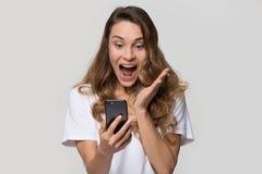 Mujer joven emocionada sorprendente por venta móvil increíble del app que hace compras imagenes de archivo