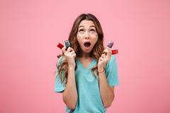 Mujer joven emocional chocada que lleva a cabo esmalte de uñas y que mira la cámara Imagenes de archivo