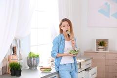 Mujer joven emocional que come la ensalada en vez del bocadillo imagen de archivo