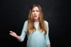 Mujer joven emocional que demuestra el descontento en el estudio Imagen de archivo