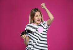 Mujer joven emocional que juega a los videojuegos con el regulador foto de archivo libre de regalías