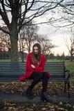 Mujer joven emocional que se sienta en un banco de parque fotografía de archivo