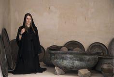Mujer joven en abaya en el medio de los potes de cocinar viejos Fotos de archivo libres de regalías