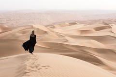Mujer joven en Abaya que presenta en paisaje del desierto Imagenes de archivo