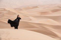 Mujer joven en Abaya que presenta en paisaje del desierto Imagen de archivo libre de regalías
