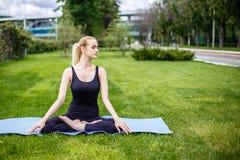 Mujer joven en actitud del loto en el parque Foto de archivo