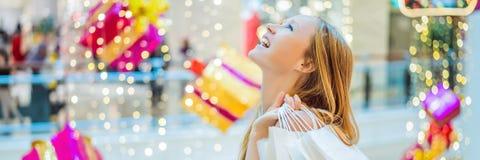 Mujer joven en alameda de la Navidad con compras de la Navidad BANDERA de los descuentos de las compras de la noche de la Navidad imagen de archivo libre de regalías