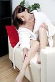 Mujer joven en albornoz en el sofá Fotos de archivo libres de regalías