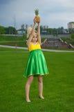 Mujer joven en alineada de color verde amarillo con la piña Fotos de archivo