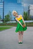 Mujer joven en alineada de color verde amarillo con la piña Imagenes de archivo