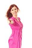Mujer joven en alineada rosada que señala un dedo en usted Foto de archivo