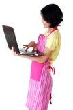 Mujer joven en appron rosado usando la computadora portátil Imagen de archivo libre de regalías