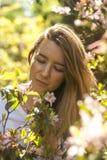 Mujer joven en arbusto floreciente en el día de verano soleado imagenes de archivo
