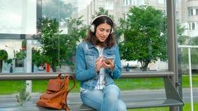 Mujer joven en auriculares que disfruta de la música, esperando el transporte público mientras que se sienta en la estación moder almacen de metraje de vídeo