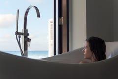 Mujer joven en bañera que admira la visión desde la ventana Destinaci?n tropical del d?a de fiesta fotos de archivo