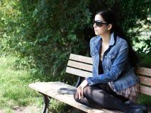 Mujer joven en banco de parque Fotos de archivo libres de regalías