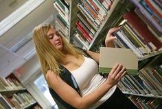 Mujer joven en biblioteca Imagen de archivo