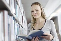 Mujer joven en biblioteca Fotos de archivo libres de regalías
