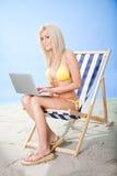 Mujer joven en bikiní usando la computadora portátil Foto de archivo libre de regalías