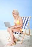 Mujer joven en bikiní usando la computadora portátil Imágenes de archivo libres de regalías