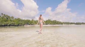 Mujer joven en bikini que camina en la agua de mar en la playa arenosa en centro turístico del paraíso Opinión de ángulo bajo Muj metrajes