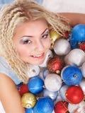 Mujer joven en bolas de la Navidad. Imagen de archivo