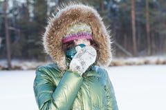 Mujer joven en bosque del invierno durante el tiempo frío que oculta su cara en bufanda al aire libre Imagenes de archivo