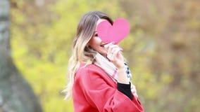 Mujer joven en bosque del otoño con el corazón de papel rojo en manos metrajes