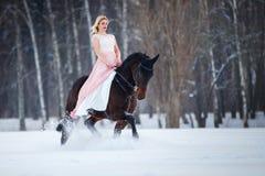 Mujer joven en caballo de montar a caballo del vestido en campo del invierno Foto de archivo