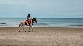 Mujer joven en caballo de montar a caballo de la playa foto de archivo