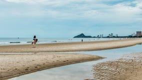 Mujer joven en caballo de montar a caballo de la playa imagen de archivo