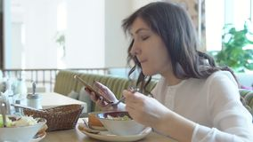 Mujer joven en café con el teléfono Hora de la almuerzo metrajes