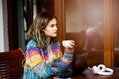 Mujer joven en café de consumición del suéter de lana colorido Fotografía de archivo