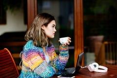 Mujer joven en café de consumición del suéter de lana colorido Fotos de archivo libres de regalías