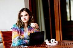 Mujer joven en café de consumición del suéter de lana colorido Imagenes de archivo