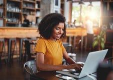 Mujer joven en café que mecanografía en el ordenador portátil imagen de archivo libre de regalías