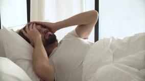 Mujer joven en cama en la mañana Hombre que duerme en cama con la alarma del teléfono almacen de video