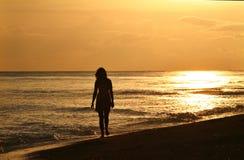 Mujer joven en caminata de la puesta del sol Imagen de archivo libre de regalías