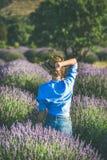 Mujer joven en camisa azul que disfruta del campo de la lavanda, Isparta, Turquía imagenes de archivo