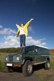 Mujer joven en campo con SUV Imagen de archivo