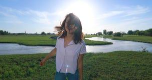 Mujer joven en campo de hierba verde con el río almacen de metraje de vídeo